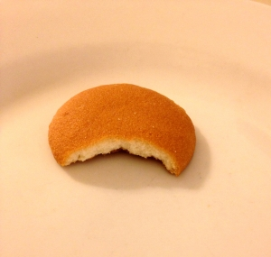 A vanilla wafer, a small, light brown, disk shaped cookie, with a bite taken out of it