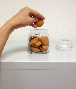 A woman's hand is suspended over a clear glass cookie jar. The jar is full of Vanilla Wafers, a small, disc shaped light brown cookie. The hand is holding a cookie (has just pulled one out of the jar).