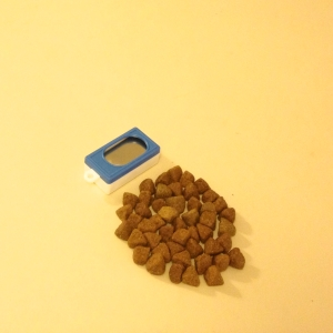A blue box clicker and pile of dry kibble